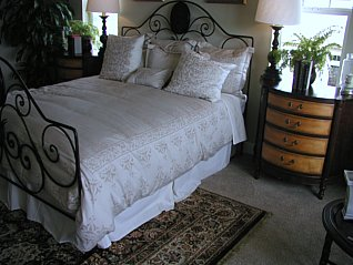 French style wrought iron bed with white linen