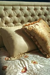 white and gold bedding and padded headboard